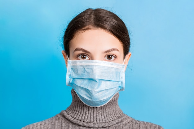 Portret Jest Ubranym Medyczną Maskę Przy Błękitem Młoda Kobieta. Chroń Swoje Zdrowie. Koncepcja Koronawirusa Premium Zdjęcia
