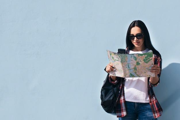 Portret jest ubranym okulary przeciwsłonecznych czyta mapę i stoi blisko błękitnej ściany uśmiechnięta kobieta Darmowe Zdjęcia