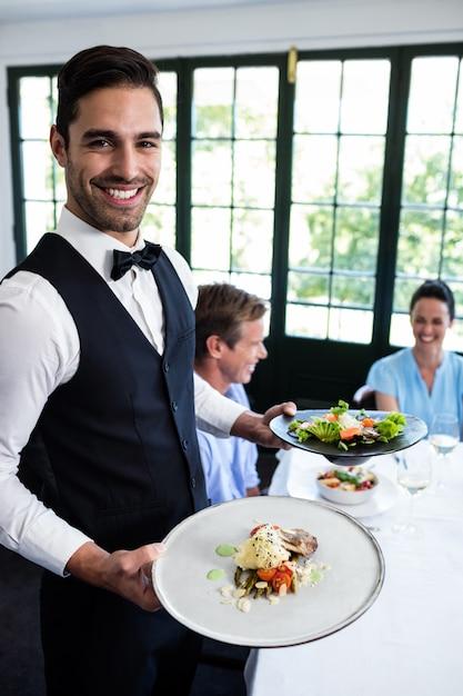 Portret kelner stoi z posiłkiem obok klientów Premium Zdjęcia