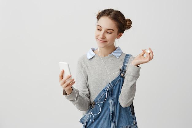 Portret Kobiety 20s Patrzeje Na Ekranie Telefon Komórkowy Z Przyjemnym Szerokim Uśmiechem. Powabny żeński Nastolatek Robi Selfie Portretowi Podczas Gdy Słuchający Muzykę Outside. Koncepcja Interakcji Darmowe Zdjęcia