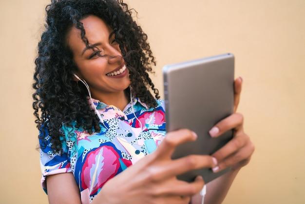 Portret Kobiety Afro Robienia Selfie Z Jej Cyfrowego Tabletu Na żółtej ścianie. Koncepcja Technologii. Premium Zdjęcia