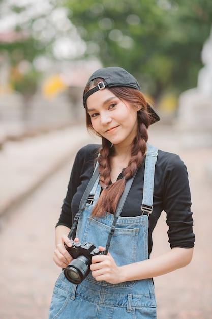 Portret kobiety azji jest profesjonalnym fotografem z aparatem bezlusterkowym Premium Zdjęcia