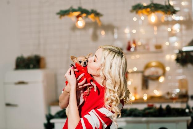 Portret Kobiety Blondynka Na Sobie Boże Narodzenie Santa Gospodarstwa Psy Chihuahua W Kostium Bożego Narodzenia W Kuchni Z Dekoracją świąteczną, Uśmiechając Się I Patrząc Na Kamery. Premium Zdjęcia