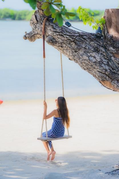 Portret Kobiety Młody Azjatykci Obsiadanie Na Huśtawkowej Arkanie I Morzu Wokoło Plażowego Dennego Oceanu Kokosowego Drzewka Palmowego Darmowe Zdjęcia