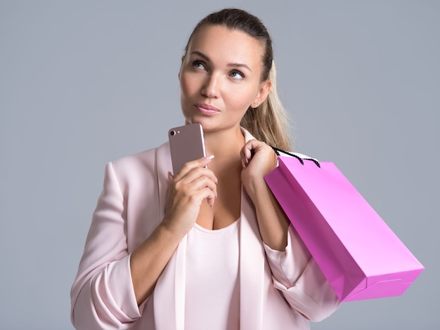 Portret Kobiety Myślenia Z Różową Torbą Na Zakupy I Telefonem Komórkowym. Darmowe Zdjęcia