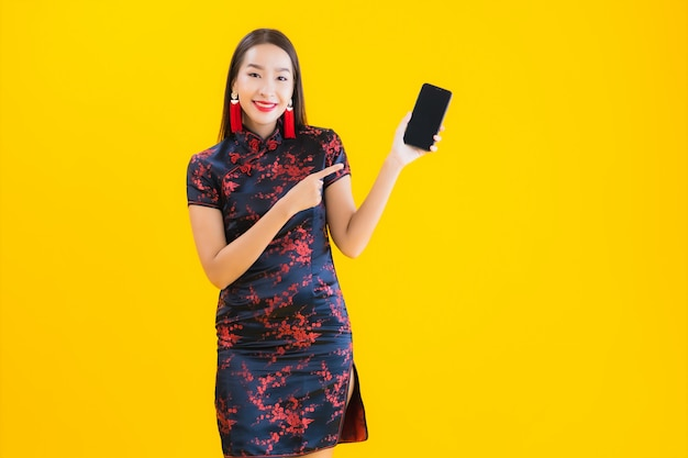 Portret Kobiety Piękni Młodzi Azjatykci Odzieży Chińczyka Sukni Use Mądrze Telefon Komórkowy Darmowe Zdjęcia
