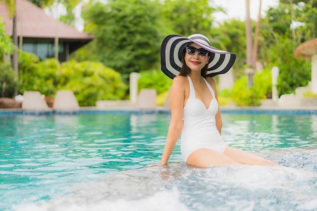 Portret kobiety piękny młody azjatykci uśmiech szczęśliwy relaksuje wokoło pływackiego basenu w hotelowym kurorcie Darmowe Zdjęcia