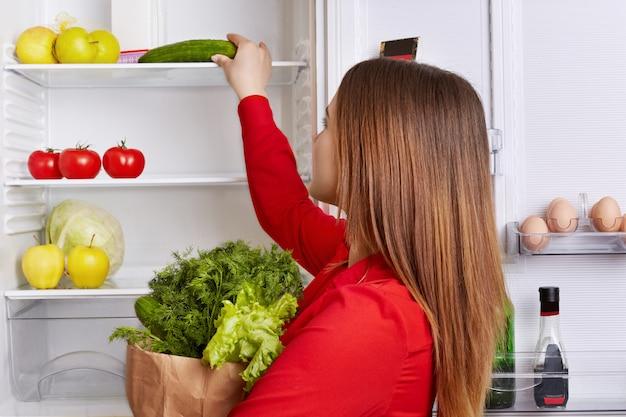 Portret Kobiety Stawia Warzywa Na Półkach Lodówki Premium Zdjęcia