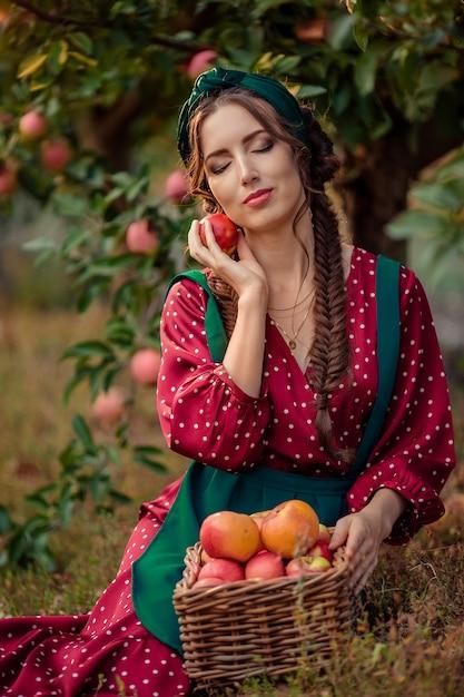 Portret Kobiety W Czerwonej Sukience, Która Siedzi Obok Wiklinowych Koszy Z Dojrzałymi Jabłkami I Trzyma Jedno Jabłko W Dłoniach, Zamykając Oczy. Zbiór W Sadzie Jabłkowym Premium Zdjęcia