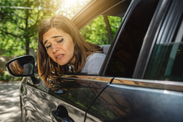 Portret Kobiety W Samochodzie Wyglądającej Przez Okno Ze Zmartwioną Miną, Być Może Z Powodu Porysowania Samochodu Podczas Parkowania Lub Wypadku Z Tyłu. Premium Zdjęcia