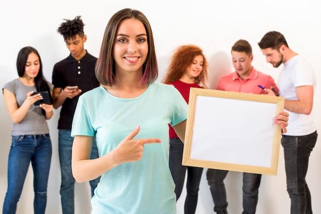 Portret kobiety wskazujące w kierunku pustej białej ramki, podczas gdy jej przyjaciele zajęci w telefon Darmowe Zdjęcia