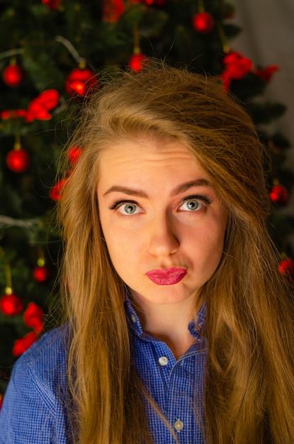 Portret Kobiety Z Jaskrawoczerwonymi Ustami, Blond Długie Włosy Na Drzewie Nowego Roku. Młoda Kobieta W Niebieskiej Koszuli Męskiej. Wakacje. Wesołych świąt. śmieszna Twarz Premium Zdjęcia