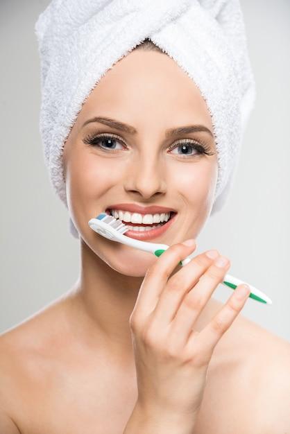 Portret kobiety z ręcznikiem na głowie za pomocą szczoteczki do zębów. Premium Zdjęcia