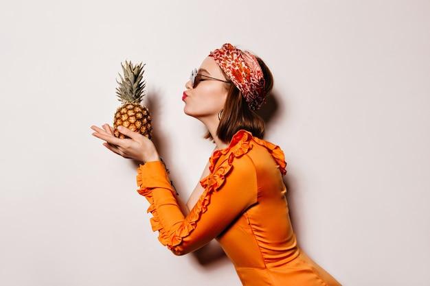 Portret Krótkowłosej Dziewczyny W Stylowej Opasce Do Włosów I Pomarańczowej Sukience Całuje Ananasa Na Białej Przestrzeni. Darmowe Zdjęcia