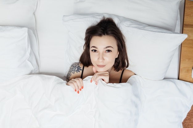 Portret ładna Dama Kłaść W łóżku Pod Białą Kołdrą I Zakrywa Jej Ciało Darmowe Zdjęcia