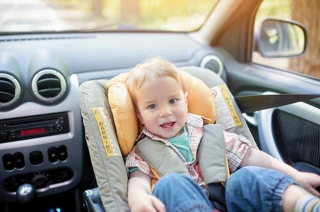 Portret ładnego 1-letniego Chłopca Siedzącego W Foteliku Samochodowym Zamontowanym Na Przednim Siedzeniu. Premium Zdjęcia