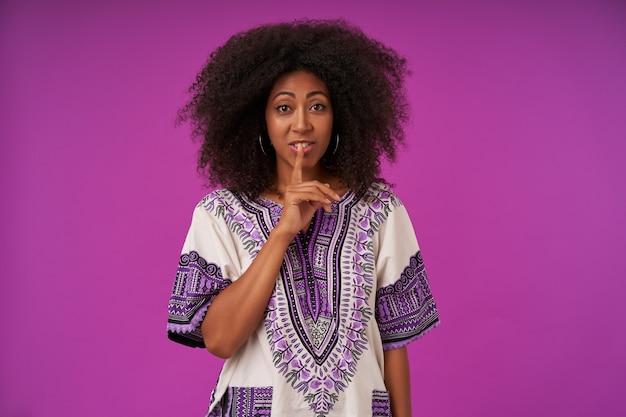Portret ładnej Młodej Kręconej Kobiety O Ciemnej Skórze W Białej Wzorzystej Koszuli, Trzymając Palec Wskazujący Na Ustach, Prosząc O Milczenie, Pozując Na Fioletowo Darmowe Zdjęcia