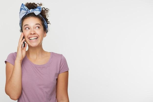 Portret ładnej Uroczej Atrakcyjnej Brunetki Z Kręconymi Włosami W Swobodnej Koszulce I Opasce, Rozmawiającej Z Kimś Specjalnym Przez Telefon Darmowe Zdjęcia