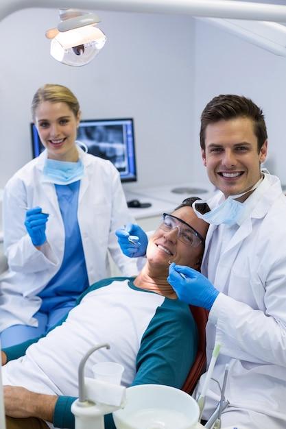 Portret Lekarzy Dentystów Badających Pacjenta Płci Męskiej Za Pomocą Narzędzi Premium Zdjęcia