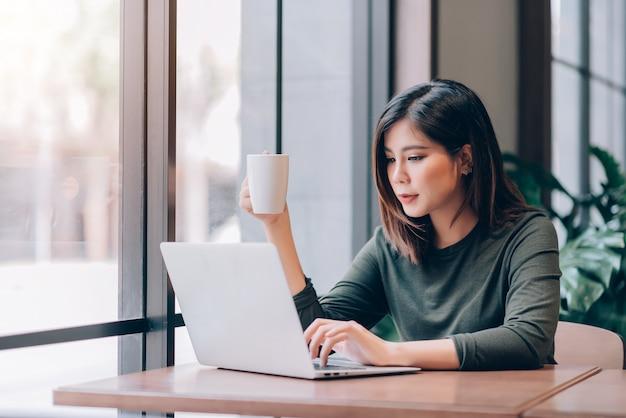Portret Mądrze Azjatycka Kobieta Freelance Trzyma Filiżankę I Pracuje Online Z Laptopem W Co-working Przestrzeni Premium Zdjęcia