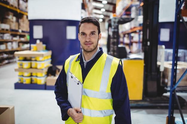 Portret magazynowy pracownik z schowkiem w magazynie Premium Zdjęcia
