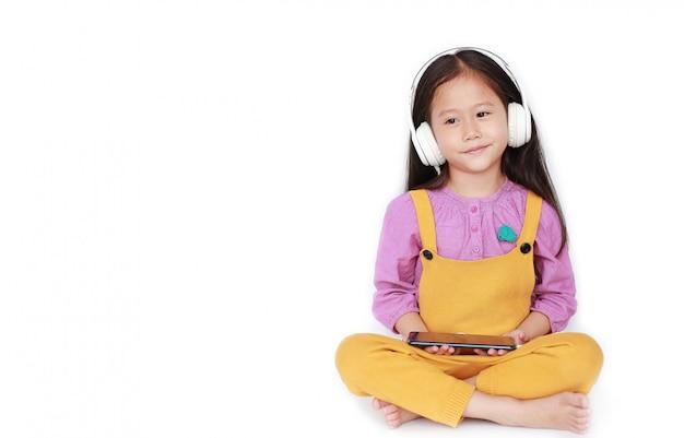 Portret Mała Azjatycka Dziewczyna Cieszy Się Słuchać Muzyka Przez Hełmofonów Premium Zdjęcia