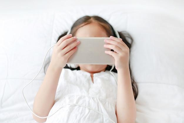 Portret Mała Azjatycka Dziewczyna Używa Hełmofony Słucha Muzykę Smartphone Podczas Gdy Kłamający Na łóżku W Sypialni W Domu. Premium Zdjęcia