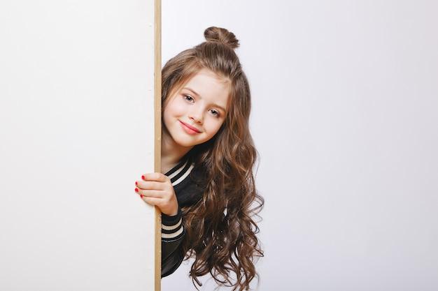 Portret Mała Modniś Dziewczyna Przyglądająca Out. Kręcone Fryzury. Miejsce Do Kopiowania Premium Zdjęcia