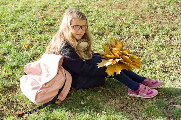 Portret mała uczennica z żółtymi liśćmi klonowymi szkolną torbą Premium Zdjęcia