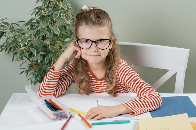Portret Mała Uśmiechnięta Dziewczyna Siedzi Przy Biurkiem W Szkłach Premium Zdjęcia