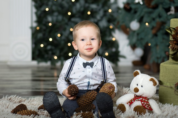 Portret małego chłopca grać z szyszek sosny w pobliżu choinki. ozdoby świąteczne. wesołych świąt i szczęśliwego nowego roku . Premium Zdjęcia