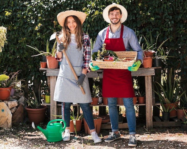 Portret Męscy I żeńscy Ogrodniczki Mienia Narzędzia I Kosz W Ogródzie Darmowe Zdjęcia