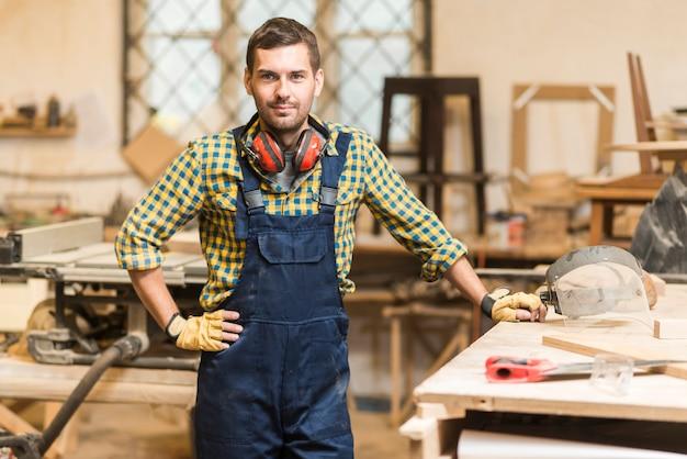 Portret męski cieśla z jego ręką na modnej pozyci blisko workbench Darmowe Zdjęcia