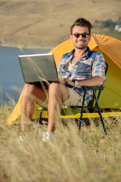 Portret Mężczyzna Z Laptopem. Campingowa Przygoda Premium Zdjęcia