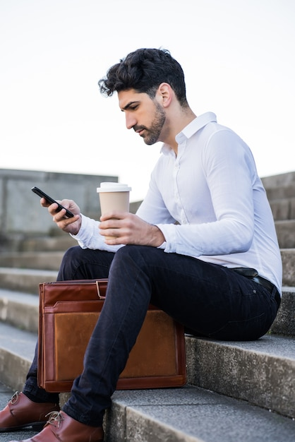 Portret Mężczyzny Biznesu Przy Użyciu Swojego Telefonu Komórkowego, Siedząc Na Schodach Na Zewnątrz Darmowe Zdjęcia