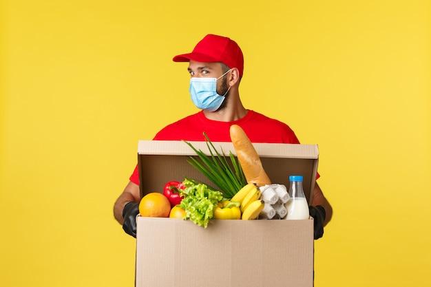 Portret Mężczyzny Dostawy Z Maską I Pudełko Spożywcze Premium Zdjęcia
