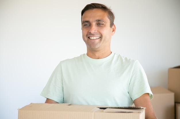 Portret Mężczyzny Rasy Kaukaskiej Przewożących Karton I Uśmiechnięty Darmowe Zdjęcia