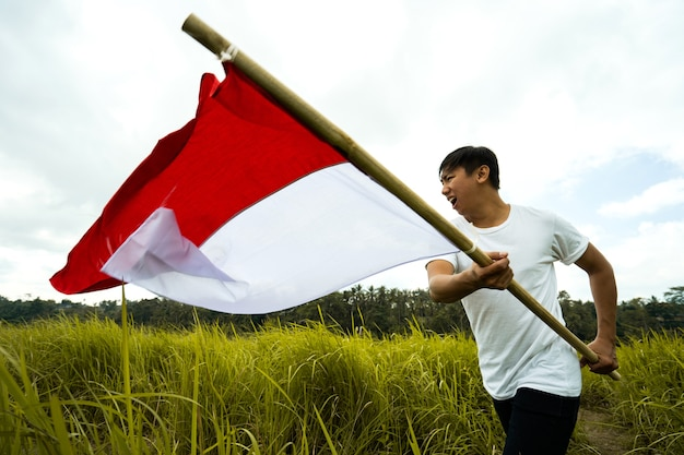 Portret Mężczyzny Trzymającego Flagę Indonezji Premium Zdjęcia