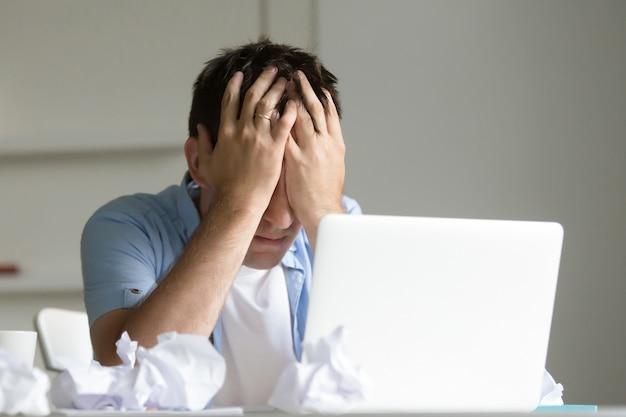 Portret mężczyzny w pobliżu komputera przenośnego, jego rąk zamknięcia jego twarzy Darmowe Zdjęcia
