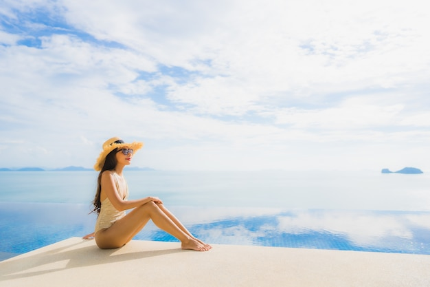 Portret młoda azjatykcia kobieta relaksuje uśmiech szczęśliwego wokoło pływackiego basenu w hotelu i kurorcie Darmowe Zdjęcia