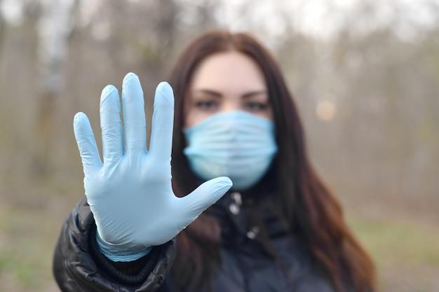 Portret Młoda Brunetki Kobieta W Błękitnej Ochronnej Maski I Gumowych Rękawiczek Przedstawieniach Zatrzymuje Gest Outdoors W Wiosny Drewnie Premium Zdjęcia