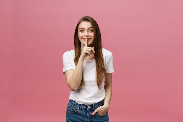 Portret młoda kobieta z palcem na wargach przeciw menchii ścianie Premium Zdjęcia