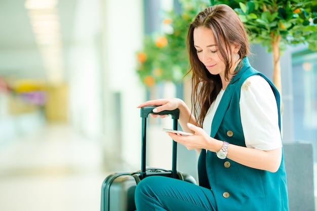 Portret Młoda Kobieta Z Smartphone W Lotnisku Międzynarodowym. Pasażer Linii Lotniczych W Poczekalni Na Lotnisku Czeka Na Samolot Premium Zdjęcia