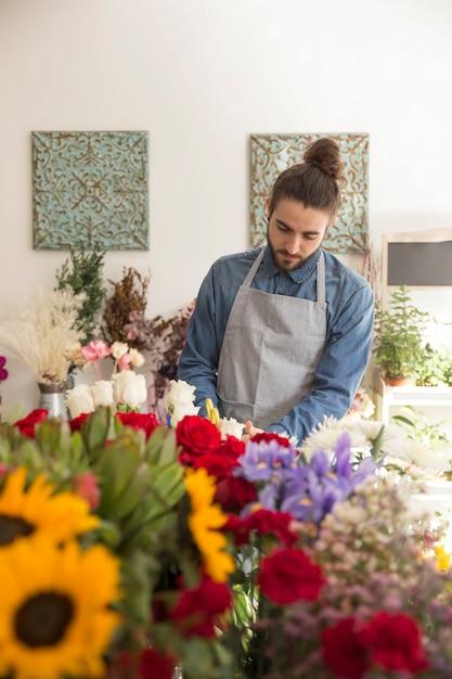 Portret Młoda Męska Kwiaciarnia W Fartuchu Bierze Opiekę Piękni Kwiaty Darmowe Zdjęcia