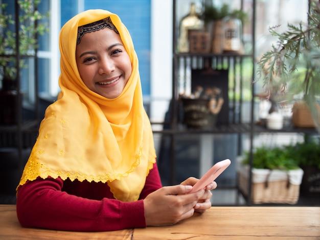 Portret młoda muzułmańska kobieta w sklep z kawą Premium Zdjęcia