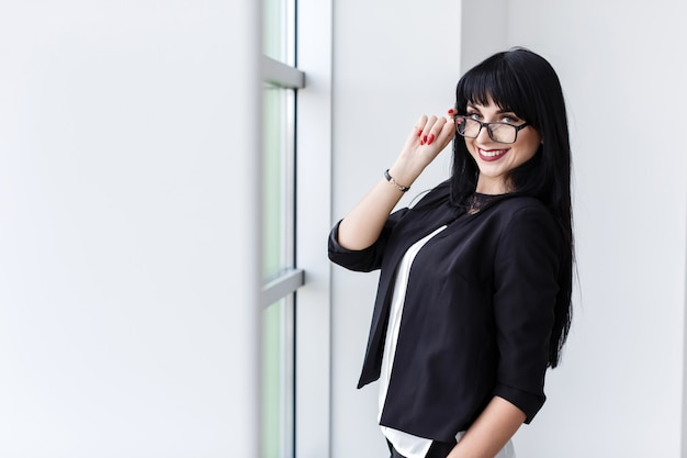 Portret młoda piękna kobieta stoi blisko okno z szkłami Premium Zdjęcia