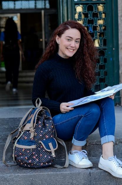 Portret Młoda Piękna Kobieta Stoi Uśmiechniętego Mienia Książka Na Miasto Ulicie. Premium Zdjęcia