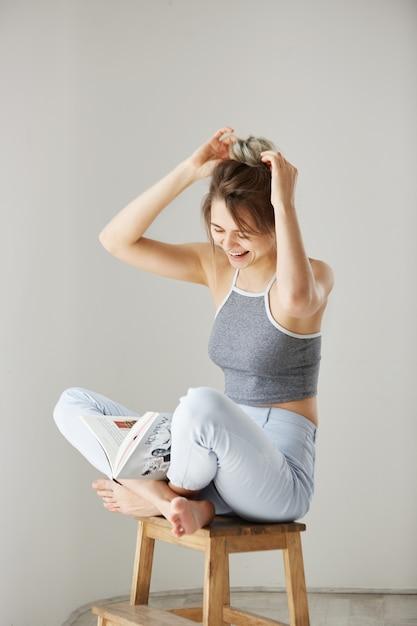 Portret Młoda Piękna Szczęśliwa Kobieta Uśmiecha Się śmiać Się Korygujący Włosianego Babeczki Obsiadanie Na Krześle Nad Biel ścianą W Domu. Darmowe Zdjęcia