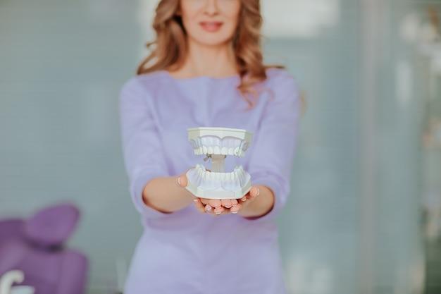 Portret Młodego Atrakcyjnego Lekarza Dentysty Z Długimi Kręconymi Włosami W Fioletowym Mundurze Medycznym Z Plastikowymi Ustami W Gabinecie. Premium Zdjęcia