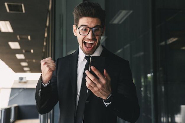 Portret Młodego Biznesmena, Ubrany W Strój Formalny, Stojącego Na Zewnątrz Budynku Ze Szkła I Trzymając Telefon Komórkowy Premium Zdjęcia